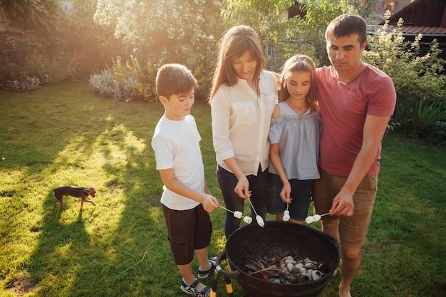 家族のバーベキューの近くに立って、公園でマシュマロを焙煎 無料写真