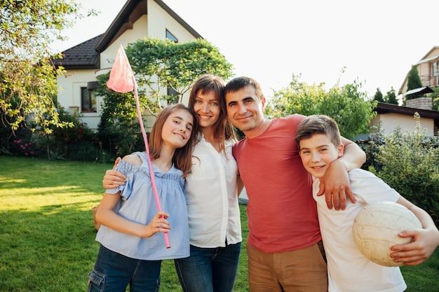 公園の緑の自然に一緒にピクニック立っている陽気な家族 無料写真