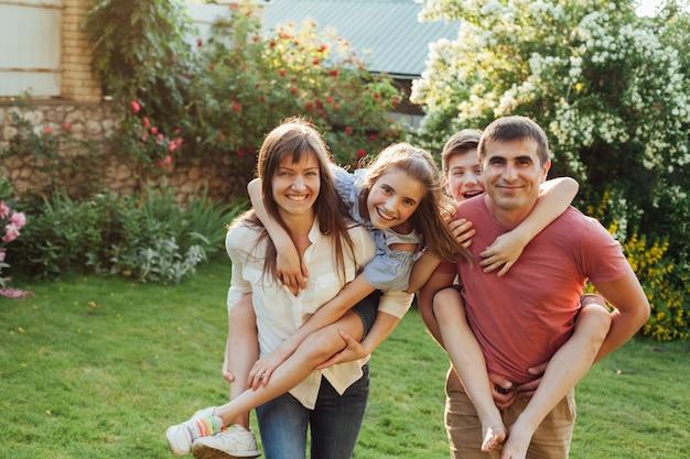 公園で子供たちにおんぶを与える両親の笑顔 無料写真