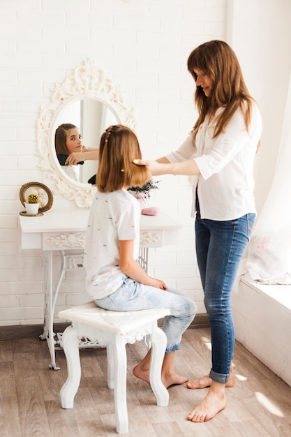 母は自宅で彼女の髪を結ぶながら鏡を見ている女の子 無料写真