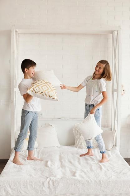 ベッドの上で戦う枕を持ついたずらな兄弟 無料写真