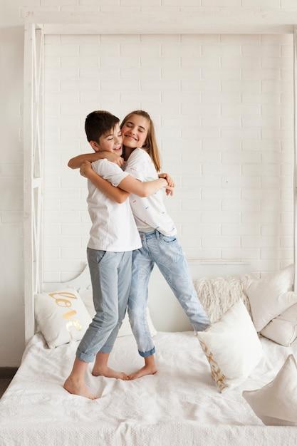 愛する兄と妹が自宅のベッドで抱きしめる 無料写真