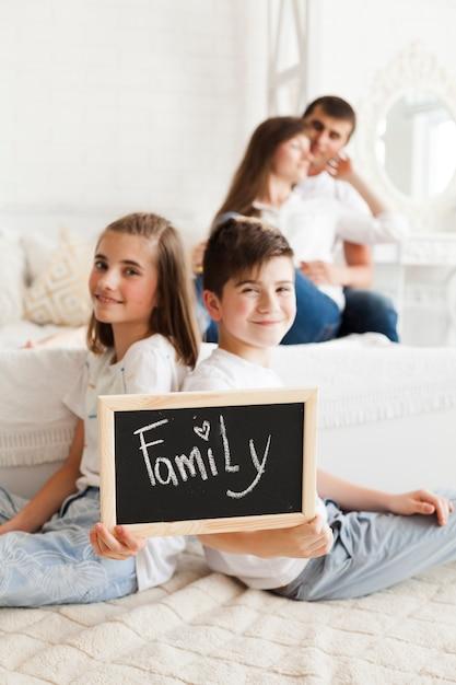 Расфокусировать романтическую пару за сланцем, держащим сестру, с семейным текстом Бесплатные Фотографии