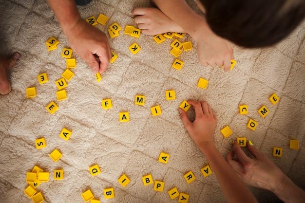 敷物のカーペットの上のスクラブルゲーム文字を持っている手のオーバーヘッドビュー 無料写真