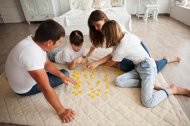 遊び心のある家族が自宅でスクラブルゲームをプレイ 無料写真