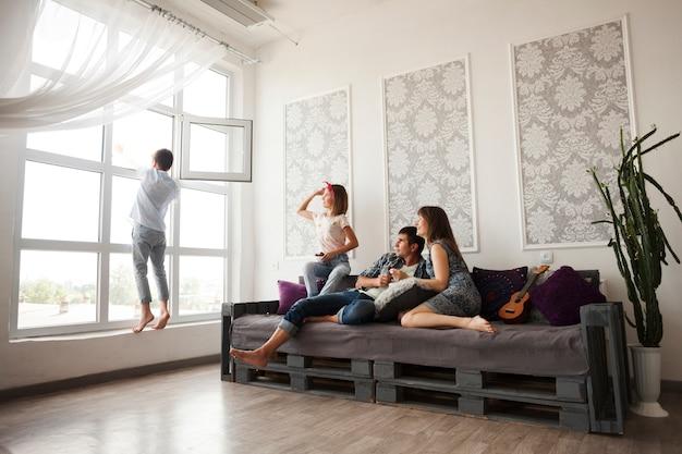 ソファに座って、窓から何かを投げる彼らの息子を見て親 無料写真