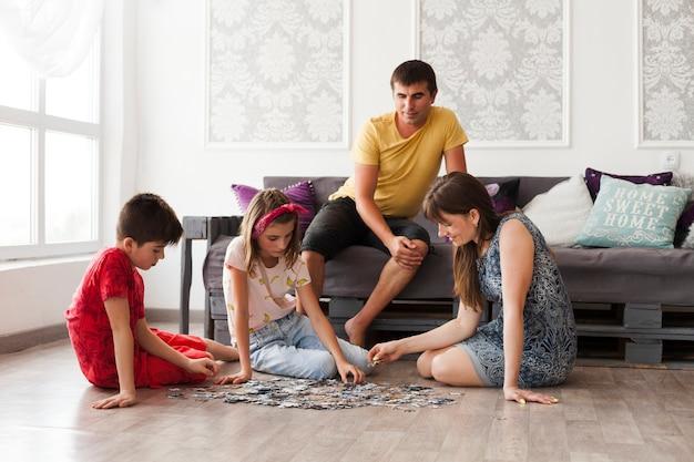 男はソファーに座っていると彼の妻とジグソーパズルを家庭で遊んでいる子供たちを見て 無料写真