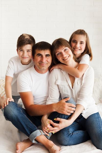 家族一緒にベッドの上に座っているとカメラ目線の笑顔 無料写真