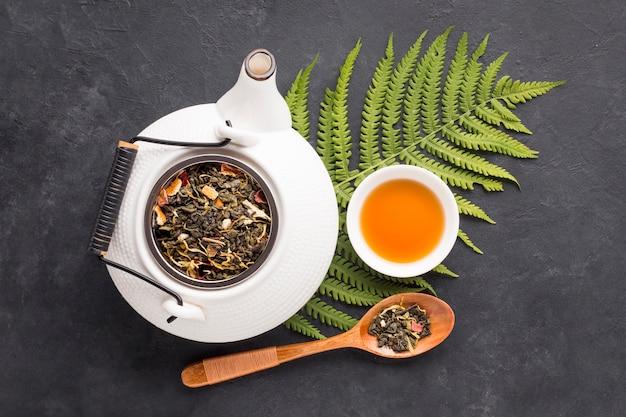 Сухие листья травы и листья папоротника с травяным чаем на черной поверхности Бесплатные Фотографии