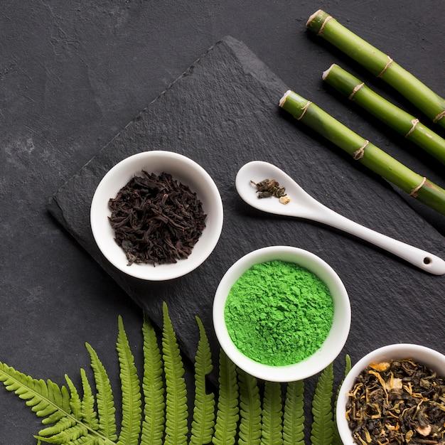 緑の抹茶と乾燥茶ハーブ竹スティックと黒い石の背景 無料写真