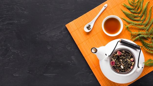 シダの葉と黒の背景にオレンジ色のプレースマットにティーポットと乾燥茶ハーブ 無料写真