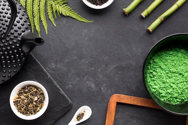 抹茶ティーパウダー。乾燥ハーブ。ティーポットスレートの石の背景にシダの葉と竹の棒 無料写真