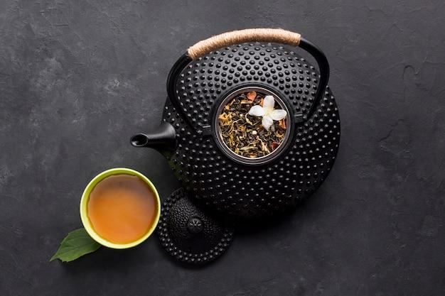 Чашка чая с ароматной сухой травой и чайником на черной поверхности Бесплатные Фотографии
