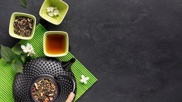 Сырой ингредиент травяного чая с чайником на зеленом коврике на черной поверхности Бесплатные Фотографии