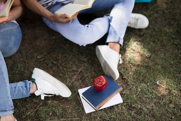 草の上に座ってノートを読む学生 無料写真