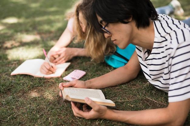 Многорасовых студентов с книгами на зеленой траве Бесплатные Фотографии