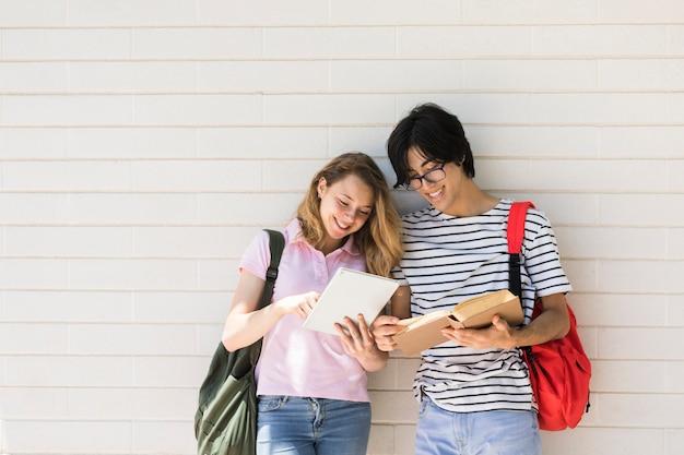 タブレットを使用して白い壁に本を読んで多民族カップル 無料写真