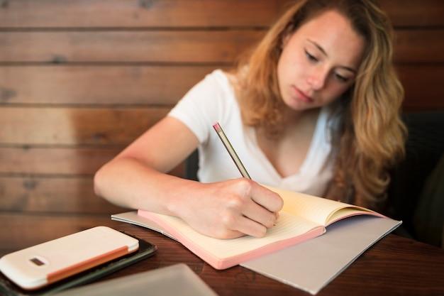魅力的な若い女性はノートを書く 無料写真