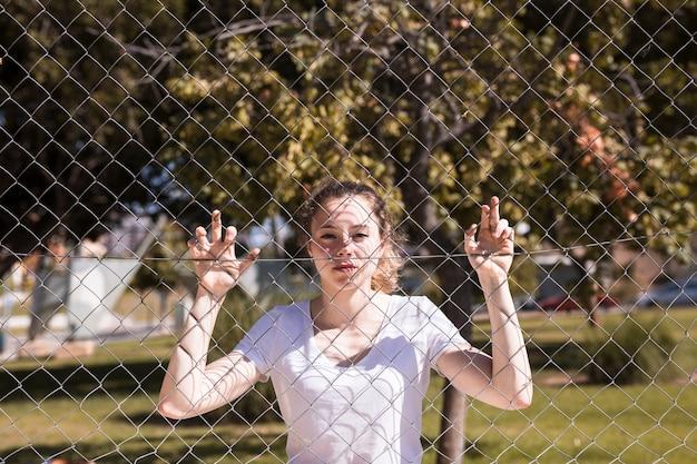 Молодая девушка держится за металлическую сетку Бесплатные Фотографии