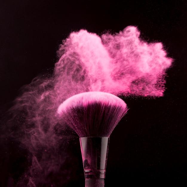 暗い背景に粉のほこりで化粧をするためのブラシ 無料写真