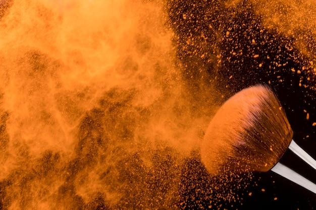 オレンジ色の乾燥粉末粒子とブラシの凍結運動 無料写真