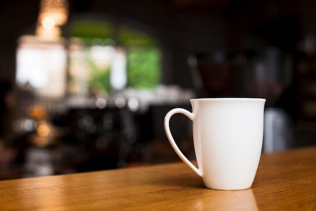 デフォーカス背景を持つ木製の机の上のコーヒーのマグカップ 無料写真