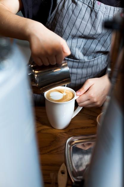 カフェでコーヒーを飲みながらプロのバリスタ注ぐラテ泡 無料写真