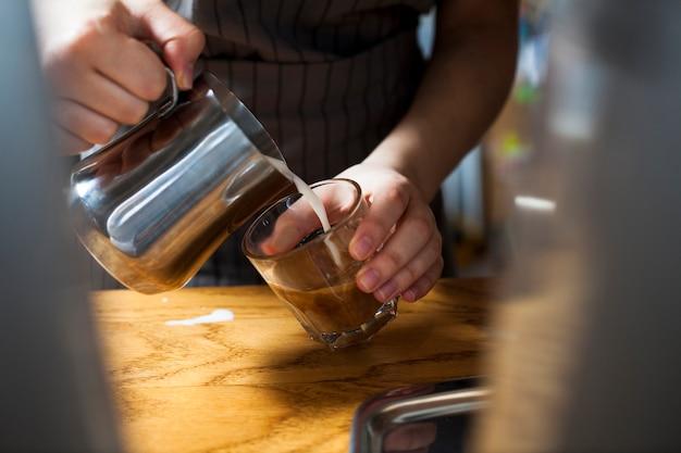 木製のテーブルの上のラテコーヒーを準備するバリスタ手のクローズアップ 無料写真