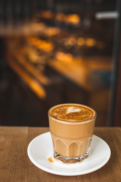 コーヒーショップで木製のテーブルの上の愛の芸術とおいしいカフェラテのガラス 無料写真