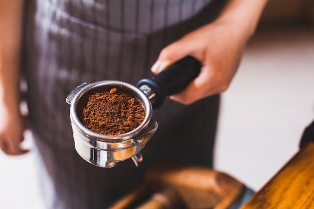 コーヒーの粉とエスプレッソスクープを持つ女性のバリスタ手のクローズアップ 無料写真