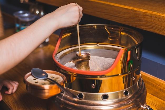 人間の手がカフェで砂の上のトルココーヒーを作る 無料写真