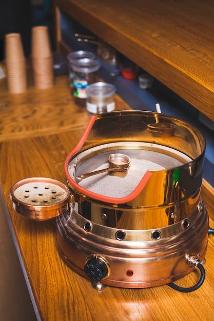 コーヒーショップで木製の机の上の熱い砂の上のトルココーヒー 無料写真