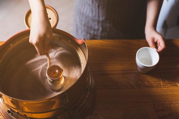 砂の中のトルココーヒーを準備する女性の手の上から見る 無料写真