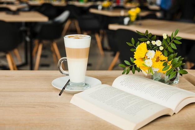 ラテコーヒーカップと木製のテーブルの上の新鮮な花瓶の本を開く 無料写真