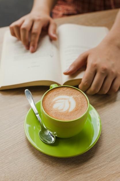 机の上の本を読んでいる人の近くのラテアートと新鮮なラテコーヒー 無料写真