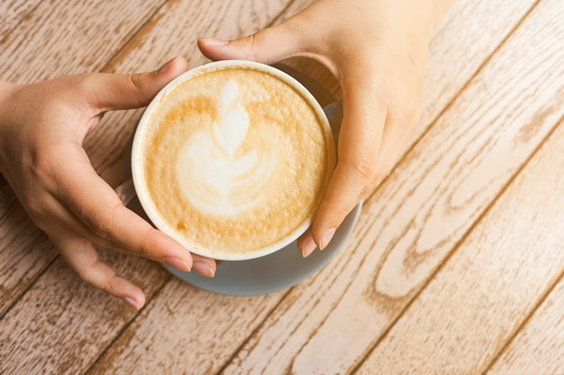 木製の表面にラテコーヒーカップをかざす人間の手の上から見る 無料写真