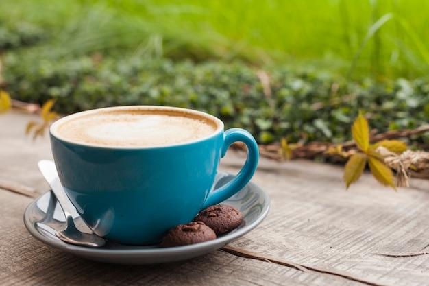 コーヒーカップとデフォーカス緑の自然の背景を持つ木製の表面上のクッキー 無料写真