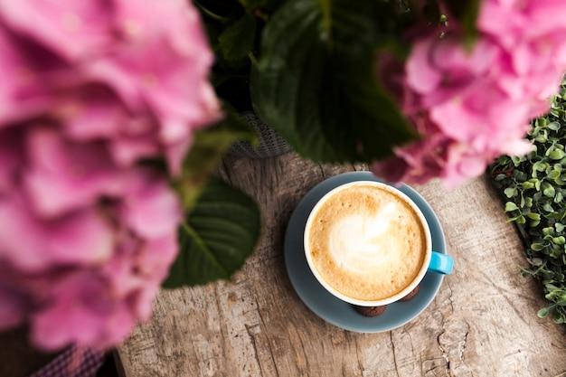 木の表面にピンクの花と泡立った泡とおいしいコーヒーのトップビュー 無料写真