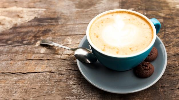 木製の机の上のおいしいクッキーとカフェラテコーヒーカップ 無料写真
