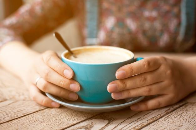 テーブルの上の泡とコーヒーのカップを保持している女性の手 無料写真