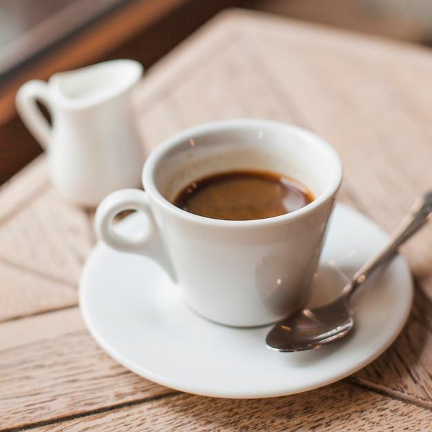 カフェの木製のテーブルの上のコーヒーカップのクローズアップ 無料写真