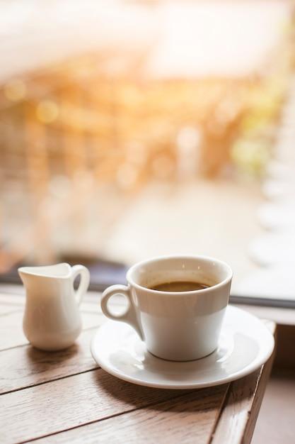 Кувшин молока и чашка кофе на деревянном столе возле стеклянного окна Бесплатные Фотографии
