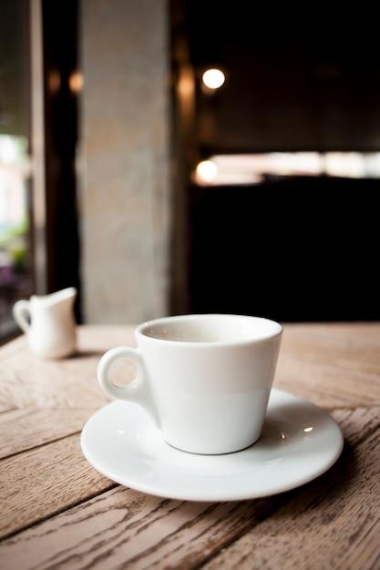 木製のテーブルの上の受け皿と白いセラミックコーヒーカップ 無料写真