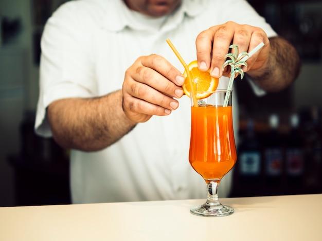 Мужской бармен, украшающий экзотический коктейль Бесплатные Фотографии