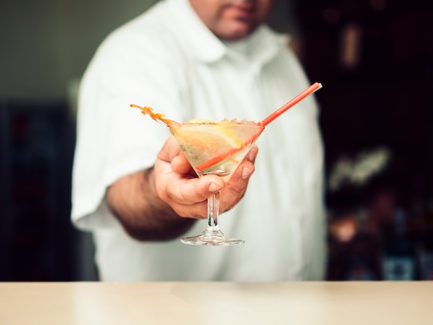 マティーニグラスでカクテルを提供する男性バーテンダー 無料写真