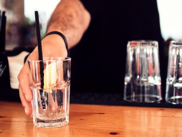 透明な飲み物の男性バーテンダーサービンググラス 無料写真