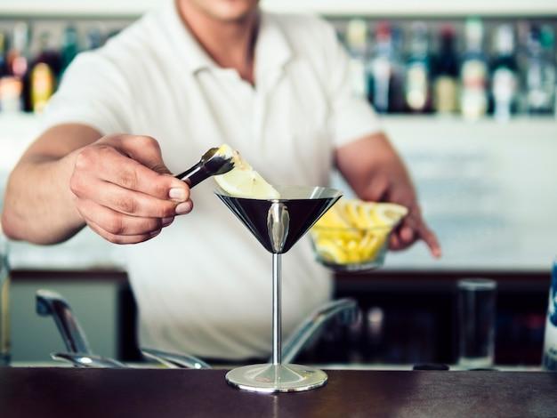 ステンレスマティーニグラスでカクテルを提供する男性のバーテンダー 無料写真