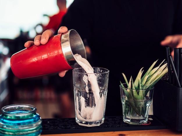Безликий бармен, наполняя стакан молочным коктейлем в баре Бесплатные Фотографии