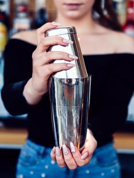 女性バーテンダーがシェーカーで飲み物を準備 無料写真