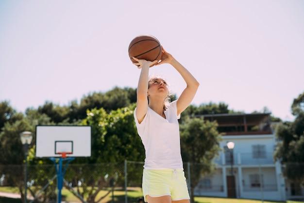 Активный подросток играет в баскетбол на корте Бесплатные Фотографии